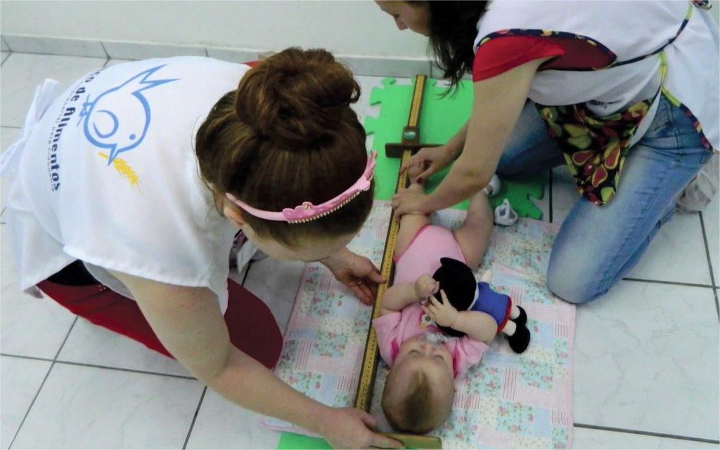 voluntárias do projeto Primeiros Passos fazem medições em bebê durante atividade em creches