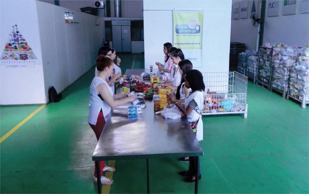 educadores e voluntárias selecionam os alimentos doados para o projeto Primeiros Passos